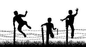 The newest Olympic tradition. Photo credit: silhouettes of three boys jumping over a barbed wire fence // ShutterStock