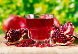 Photo credit: glass of pomegranate juice with fresh fruits on wooden table // ShutterStock