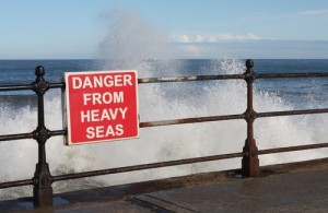 Photo credit: Breaking waves on promenade with warning sign // ShutterStock