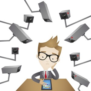 Vector illustration of a cartoon businessman sitting at his desk surrounded by surveillance cameras spying on him.
