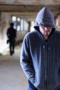 shutterstock / mr.kornflakes Smoking Criminal with Hood Walking in a Slum Corridor