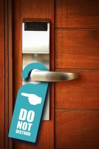"""Photo credit: """"Do not disturb sign hang on door knob"""" // ShutterStock"""