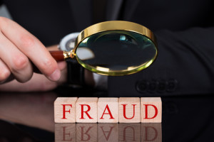 Photo credit: Cropped image of young businessman examining Fraud blocks through magnifying glass on desk // ShutterStock