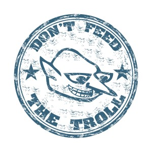 sutterstock / oxlock: Blue grunge rubber stamp with a troll face and the text do not feed the troll written with capital letters