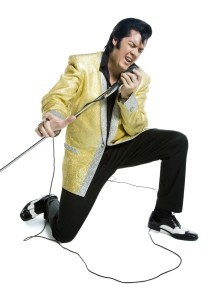 Alan Bailey/Shutterstock - An Elvis impersonator singing into a microphone