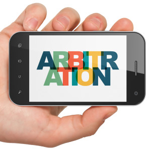 Maksim Kabakou - shutter stock Law concept: Hand Holding Smartphone with Painted multicolor text Arbitration on display